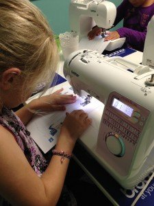 Girl learning proper use of the sewing machine.