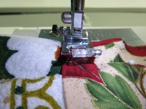 Following the left side of the presser foot, sew the handle to the towel.